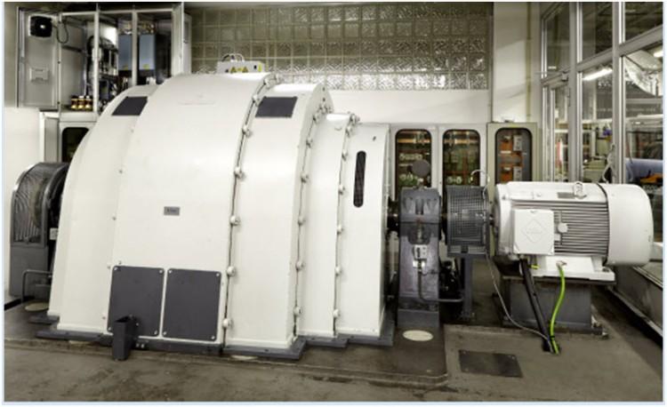 Po prawej generator udarowy w laboratorium badawczym I²PS GmbH; po lewej, za otwartą szafą rozdzielczą z rozwiązaniem napędowym Eaton, widoczny nowy silnik asynchroniczny.