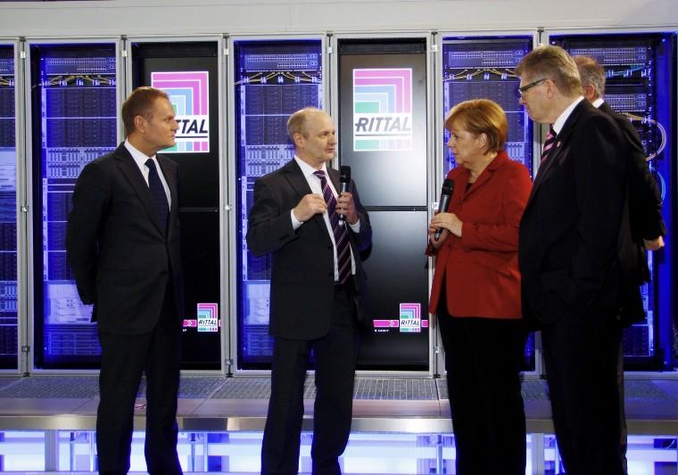 Friedhelm Loh wita niemiecką kanclerz Angelę Merkel oraz polskiego szefa rządu Donalda Tuska na stoisku targowym Rittal.