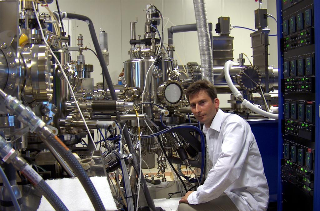 W Instytucie Fizyki Doświadczalnej Wydziału Fizyki Uniwersytetu Warszawskiego opracowano, skonstruowano i przetestowano nowatorskie kropki kwantowe z pojedynczymi jonami kobaltu. Na zdjęciu dr Wojciech Pacuski przy aparaturze do epitaksji z wiązek molekularnych użytej do budowy kropek kwantowych. Źródło: FUW